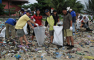 Participants of the beach clean-up using two different types of bags to separate recyclable products from non-recyclable products.