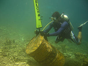 A diver extracting an oil drum found marooned among the reefs off Pulau Sibuan.