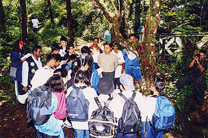 Lasal Asirvatham teaching a group of students during a field trip.