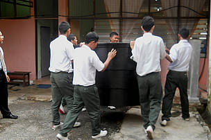 Students assisting to set-up the water tank