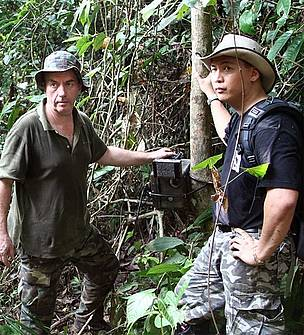 Raymond and Stephen checking the video camera trap in the forest